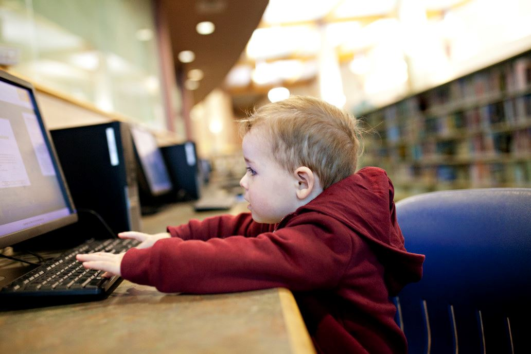 Toddler working at computer in the library