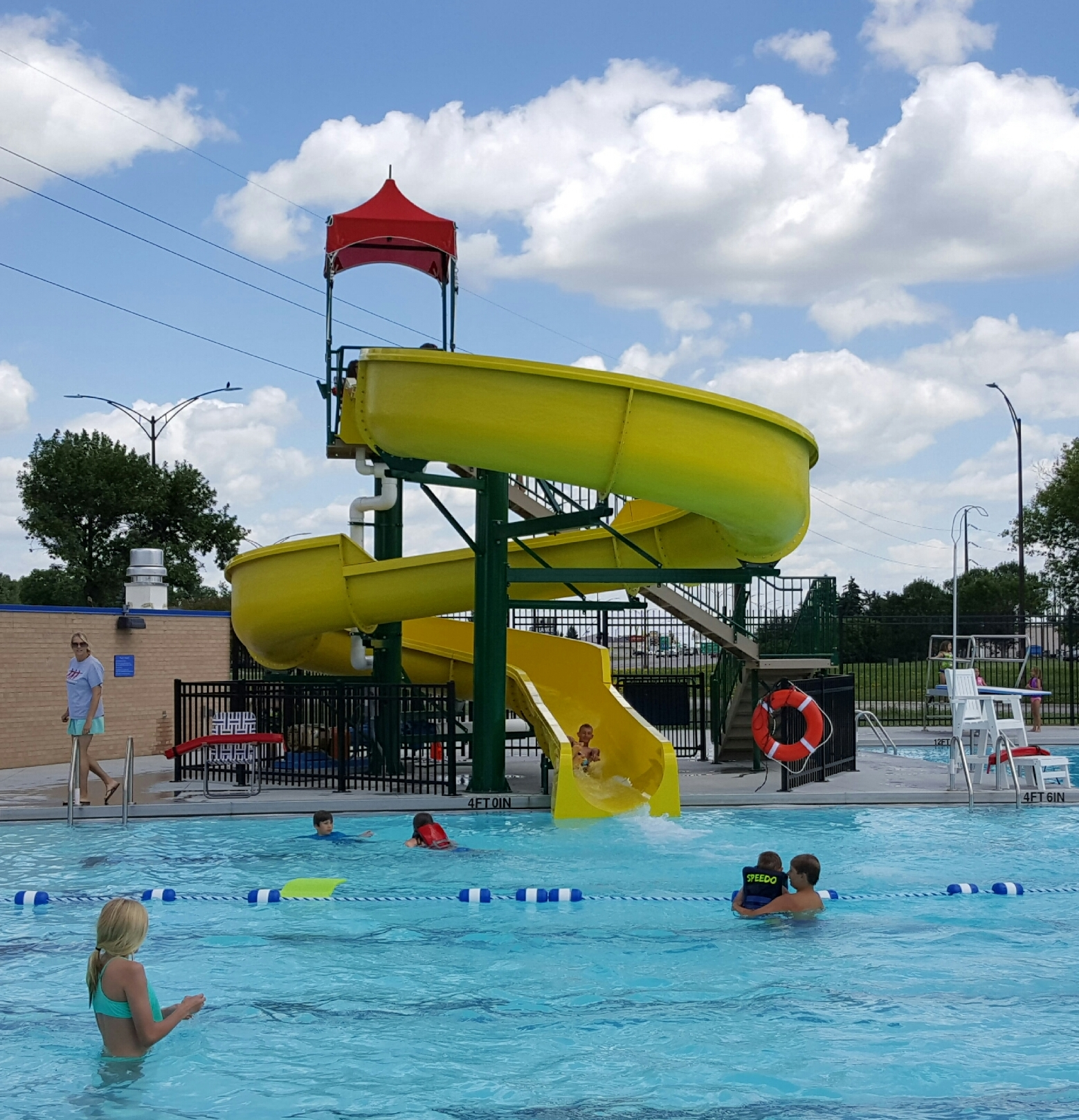People swimming in a pool that has a slide feature